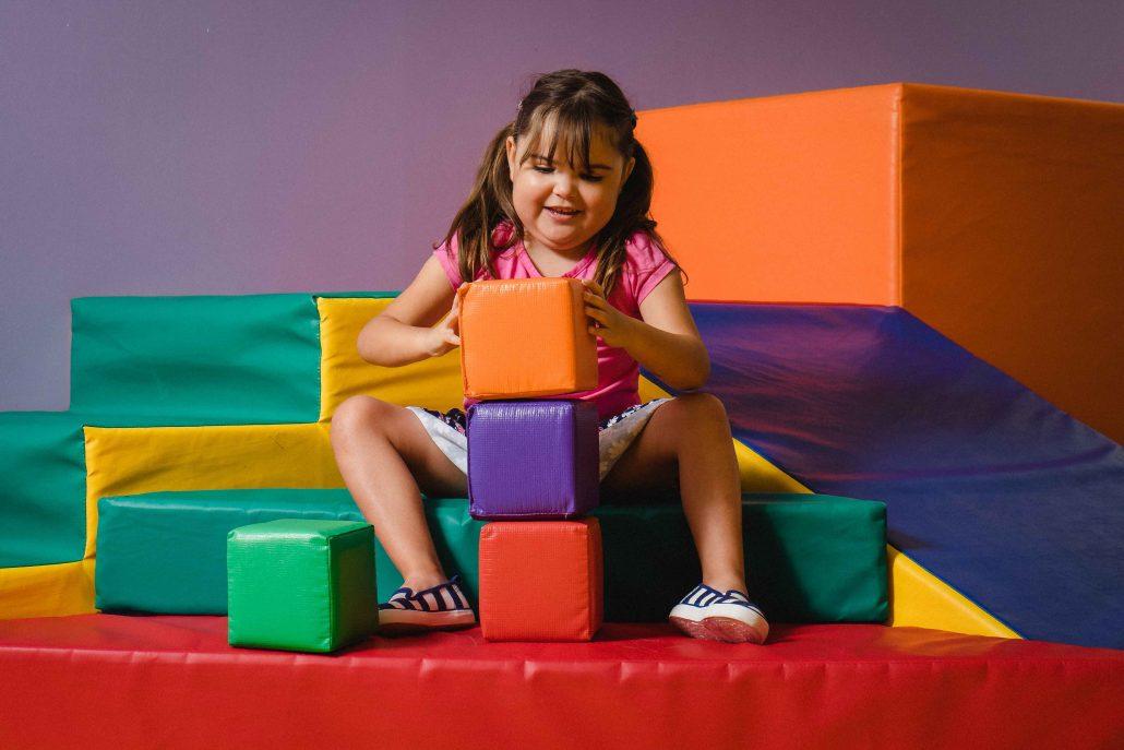 Fillette heureuse jouant avec de gros blocs colorés