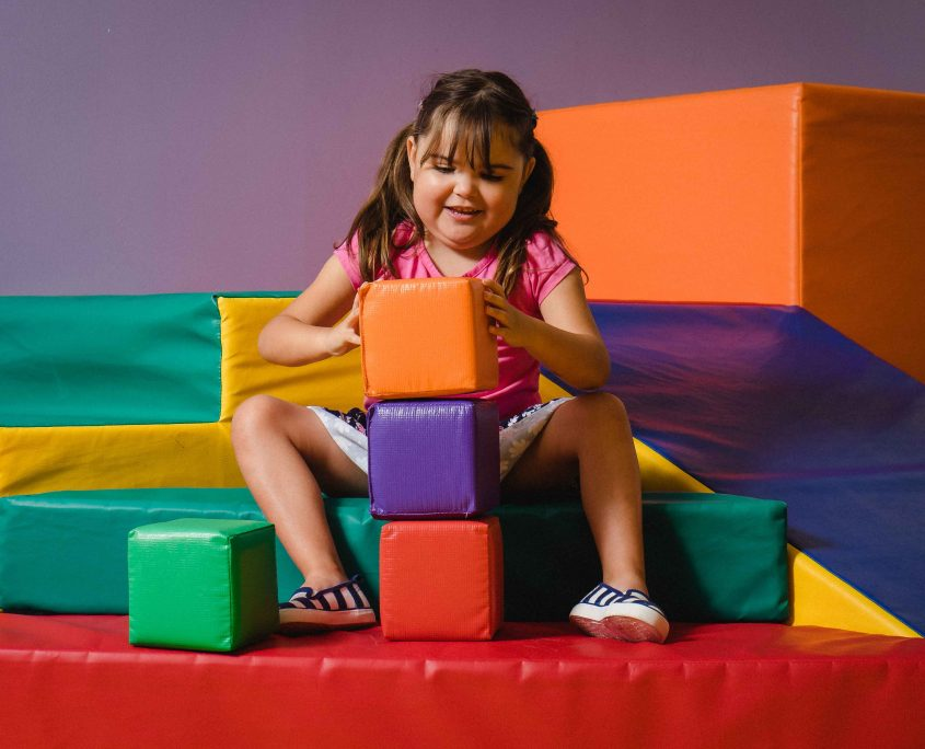 happy girl playing with big colourful blocks