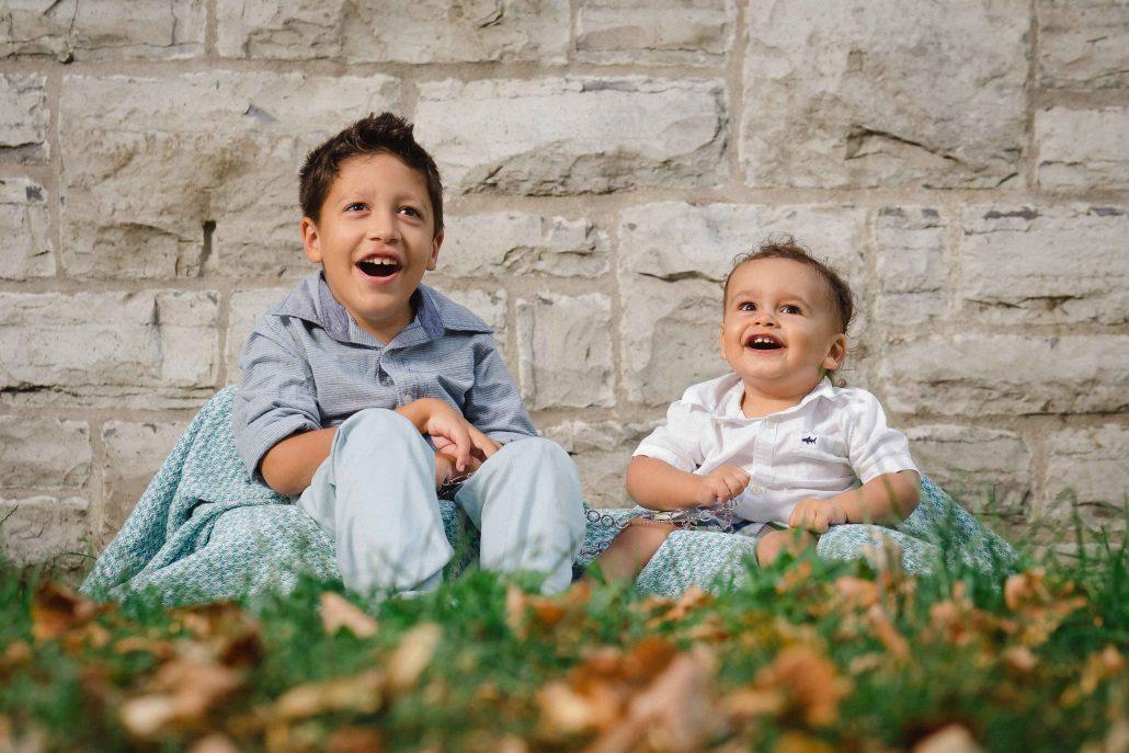 Garçon et bébé assis dans l'herbe devant un mur en pierres calcaires.