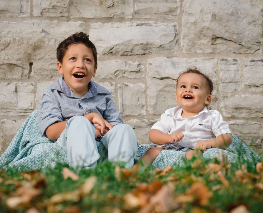 Boy and baby in the grass infront of a limestone wall