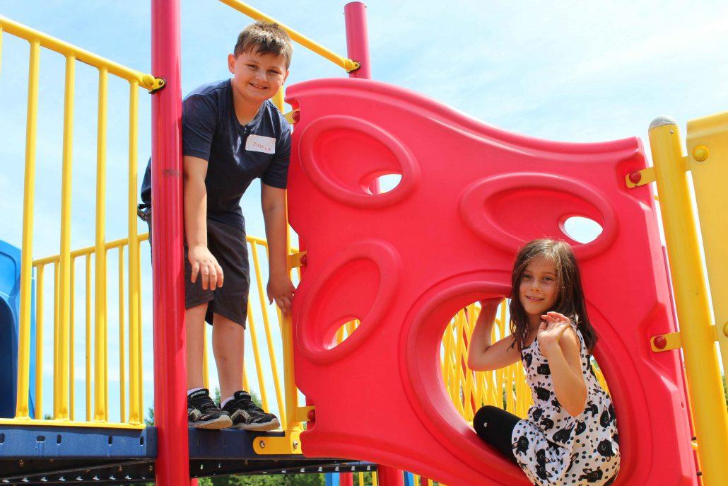 Garçon et fille jouant sur une structure de jeux.
