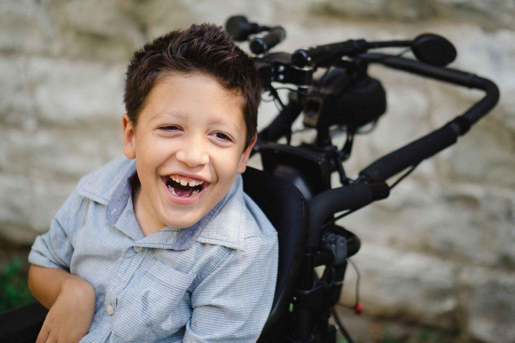 Garçon souriant assis dans un fauteuil roulant