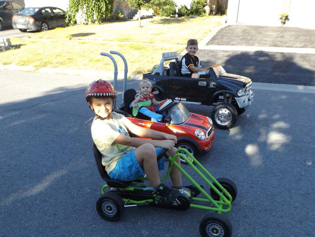 Kate jouant dans une voiturette à batterie avec ses frères